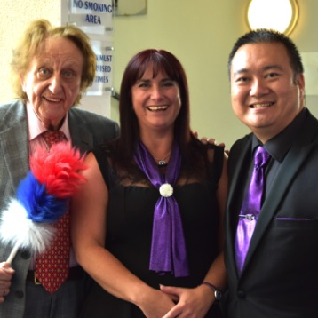 "SingMe Merseyside's appearance at the Liverpool Empire Theatre for the launch of ""Prompt"" - an industry guide to the theatre and entertainment business. SingMe Founder and Musical Director, Billy Hui and SingMe Choir Manager and Administrator, Wendy Williamson, pictured here with the legendary Ken Dodd!"